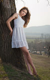 Retrato hermoso de la muchacha con el sombrero cerca de un árbol en el jardín. Mujer sensual caucásica joven en un paisaje románti Fotografía de archivo libre de regalías