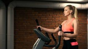 Retrato hermoso de la mujer en el ciclo del gimnasio almacen de metraje de vídeo