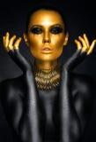 Retrato hermoso de la mujer en oro y colores negros foto de archivo