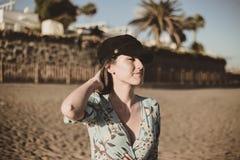 Retrato hermoso de la mujer joven en el desierto que toca su pelo con un casquillo negro foto de archivo