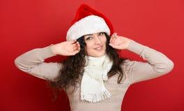 Retrato hermoso de la mujer joven en el sombrero del ayudante de santa que presenta en rojo Imágenes de archivo libres de regalías
