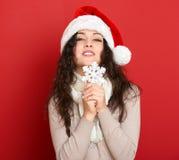Retrato hermoso de la mujer joven en sombrero del ayudante de santa con el copo de nieve grande que presenta en rojo Imagen de archivo