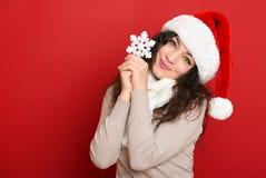 Retrato hermoso de la mujer joven en sombrero del ayudante de santa con el copo de nieve grande que presenta en rojo Fotografía de archivo