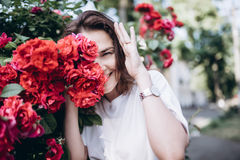 Retrato hermoso de la mujer joven morena sensual en el vestido blanco cerca de rosas rojas imágenes de archivo libres de regalías