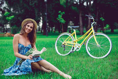 Retrato hermoso de la mujer joven que lee un libro con la bicicleta en el parque foto de archivo
