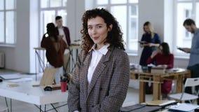 Retrato hermoso de la mujer de negocios europea joven que toca el pelo rizado en el traje formal, sonrisa feliz en la oficina mod almacen de video