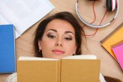 Retrato hermoso de la mujer que miente en el libro de lectura del piso fotos de archivo libres de regalías