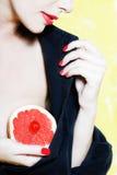 Retrato hermoso de la mujer que muestra el pecho del pomelo Foto de archivo libre de regalías