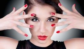 Retrato hermoso de una muchacha con los labios y los clavos rojos Imagenes de archivo