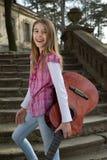 Retrato hermoso de una muchacha sonriente amistosa despreocupada con la guitarra Imagenes de archivo