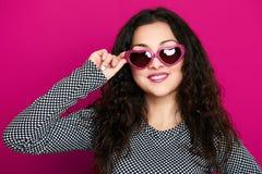 Retrato hermoso del encanto de la muchacha en el rosa en gafas de sol de la forma del corazón, pelo rizado largo Imagen de archivo
