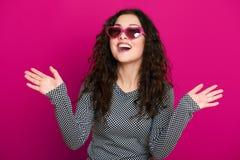 Retrato hermoso del encanto de la muchacha en el rosa en gafas de sol de la forma del corazón, pelo rizado largo Fotos de archivo libres de regalías