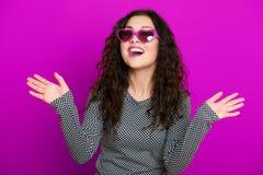 Retrato hermoso del encanto de la muchacha en la púrpura en gafas de sol de la forma del corazón, pelo rizado largo Foto de archivo libre de regalías