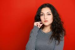 Retrato hermoso en rojo, pelo rizado largo del encanto de la muchacha Imagenes de archivo