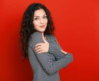 Retrato hermoso en rojo, pelo rizado largo del encanto de la muchacha Imagen de archivo