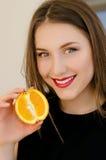 Retrato hermoso joven del primer de la muchacha con la fruta anaranjada, el lápiz labial rojo y el maquillaje perfecto Imágenes de archivo libres de regalías
