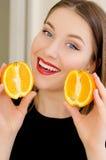 Retrato hermoso joven del primer de la muchacha con la fruta anaranjada, el lápiz labial rojo y el maquillaje perfecto Fotos de archivo libres de regalías