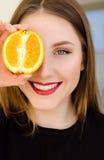 Retrato hermoso joven del primer de la muchacha con la fruta anaranjada, el lápiz labial rojo y el maquillaje perfecto Foto de archivo