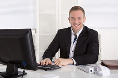 Retrato: Hombre de negocios joven hermoso en la sonrisa que se sienta del traje adentro foto de archivo libre de regalías