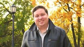 Retrato Hombre gordo en parque que sonríe en la cámara almacen de metraje de vídeo