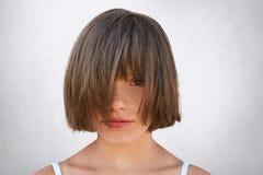 Retrato horizontal da criança fêmea freckled pequena que cobre sua cara com o cabelo ao poising contra o muro de cimento branco A fotografia de stock