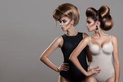 Retrato horizontal de dos mujeres atractivas con el peinado creativo Foto de archivo