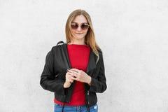Retrato horizontal de la hembra de moda que lleva la chaqueta negra, el suéter rojo y las gafas de sol de moda teniendo mochila e Fotografía de archivo libre de regalías