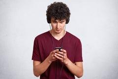 Retrato horizontal de la mensajería y de bloguear del hombre joven en el teléfono móvil mientras que música que escucha en auricu fotos de archivo