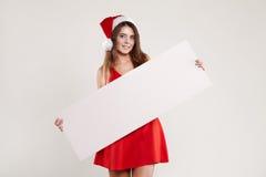 Retrato horizontal de la muchacha de la Navidad con la placa en el fondo blanco Imágenes de archivo libres de regalías