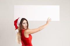 Retrato horizontal de la muchacha de la Navidad con la placa en el fondo blanco Imagenes de archivo
