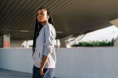 Retrato horizontal de medio cuerpo del adolescente afroamericano pensativo con los auriculares que miran a un lado Fotos de archivo libres de regalías