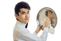 Retrato horizontal de um garçom considerável com cabelo preto que fricciona a bandeja para brilhar imagens de stock