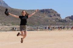 Retrato horizontal de uma jovem mulher nas férias, salto feliz acima na praia Copie o espaço fotos de stock
