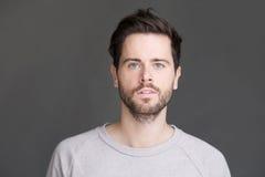 Retrato horizontal de un hombre joven con la barba que mira la cámara Imagen de archivo libre de regalías