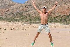 Retrato horizontal de un hombre joven el las vacaciones, salto feliz para arriba en la playa Copie el espacio Foto de archivo