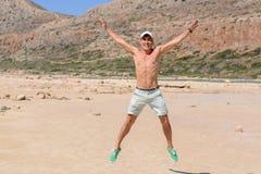 Retrato horizontal de un hombre joven el las vacaciones, salto feliz para arriba en la playa Copie el espacio Fotografía de archivo
