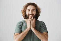 Retrato horizontal do homem oriental considerável com cabelo encaracolado e da barba que guarda as mãos no queixo ao sorrir alegr imagens de stock
