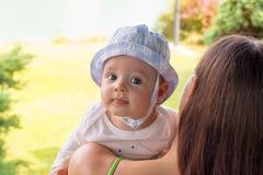 Retrato inocente da cara do bebê no chapéu do sol acima do ombro da mãe no bakcground da natureza imagens de stock