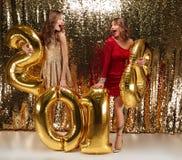 Retrato integral de dos muchachas atractivas en vestidos brillantes Fotos de archivo