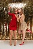 Retrato integral de dos mujeres divertidas en vestidos brillantes Fotos de archivo libres de regalías