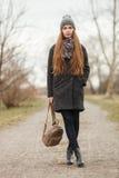 Retrato integral de la forma de vida de la mujer adulta joven y bonita con el pelo largo magnífico que presenta en parque de la c Fotografía de archivo libre de regalías