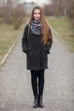 Retrato integral de la forma de vida de la mujer adulta joven y bonita con el pelo largo magnífico que presenta en parque de la c Fotografía de archivo