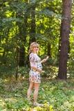 Retrato integral de la mujer embarazada joven que sostiene una piruleta en naturaleza del verano Fotografía de archivo
