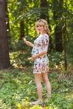 Retrato integral de la mujer embarazada joven que sostiene una piruleta en naturaleza del verano Foto de archivo