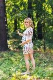 Retrato integral de la mujer embarazada joven que sostiene una piruleta en naturaleza del verano Imágenes de archivo libres de regalías