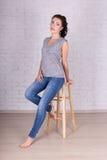Retrato integral de la mujer hermosa que se sienta en silla de madera Imagenes de archivo