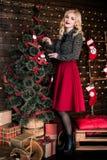 Retrato integral de la mujer joven feliz que adorna el árbol de navidad con la bola de la Navidad Fotografía de archivo
