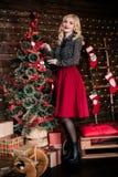 Retrato integral de la mujer joven feliz que adorna el árbol de navidad con la bola de la Navidad Foto de archivo libre de regalías