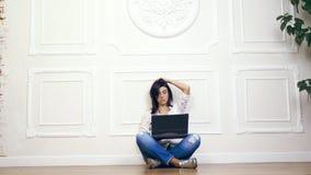 Retrato integral de la mujer joven, muchacha, morenita, en la camisa blanca y los vaqueros, trabajando en el ordenador portátil m metrajes