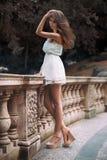 Retrato integral de la mujer modelo hermosa con las piernas largas que llevan el vestido blanco que presenta oudoors Imagen de archivo